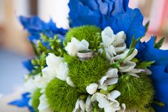 Mazzo di nozze nei colori bianchi e verdi e fedi nuziali in decorazione blu su una superficie bianca fotografia stock libera da diritti