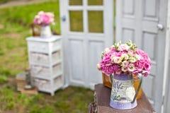 Mazzo di nozze in un annaffiatoio vicino alla decorazione delle porte di nozze Fotografia Stock