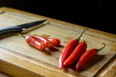 Mazzo di peperoncini rossi su un tagliere Immagini Stock