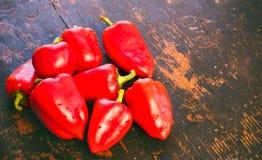 Mazzo di peperoni dolci rossi maturi freschi su un vecchio fondo di legno nero di lerciume Immagini Stock