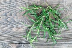 Mazzo di ramoscelli freschi dei rosmarini su fondo di legno grigio, orizzonte fotografia stock
