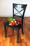 Mazzo di ranunculus su una sedia nera Fotografia Stock