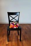 Mazzo di ranunculus su una sedia nera Immagini Stock Libere da Diritti