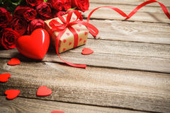 Mazzo di rose con un contenitore di regalo e un cuore rosso Immagini Stock Libere da Diritti