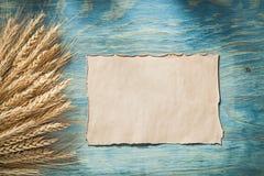 Mazzo di strato di carta d'annata delle orecchie del grano sul bordo di legno Immagine Stock Libera da Diritti