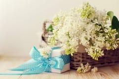 Mazzo di un lillà bianco in un canestro e di un contenitore di regalo su una superficie di legno Fotografia Stock