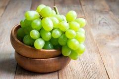 Mazzo di uva matura verde in ciotola di legno, spazio della copia Fotografia Stock
