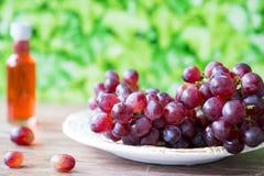 Mazzo di uva rossa sul piatto bianco, contro il fondo delle foglie verdi Spazio per testo fotografia stock libera da diritti