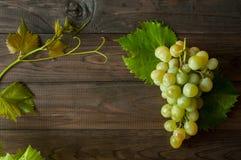 Mazzo di uva verde con le foglie sui precedenti di legno Fotografie Stock