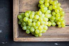 Mazzo dolce di uva verde sul fondo rustico del Th Fotografie Stock
