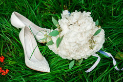 Mazzo e scarpe nuziali nell'erba Fotografia Stock