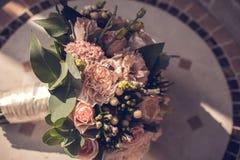 Mazzo e vetro di nozze con champagne in mani della sposa, David Austin Mazzo alla moda Mazzo delle rose porpora, crema e rosa fotografia stock libera da diritti