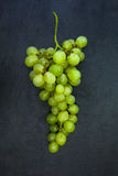Mazzo fresco di uva verde isolata sulla pietra grigio scuro dell'ardesia Immagine Stock Libera da Diritti