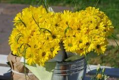 Mazzo giallo del crisantemo nel secchio di alluminio sulla via Fotografia Stock Libera da Diritti