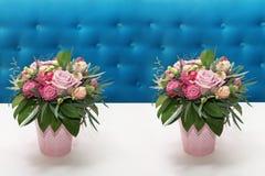Mazzo identico due dei fiori delle rose in vasi rosa su un whi immagine stock libera da diritti