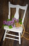 Mazzo lilla con il cuore della corda sulla sedia Fotografia Stock
