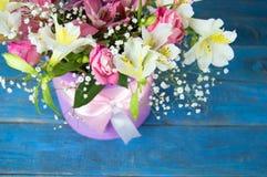 Mazzo luminoso di alstroemeria, delle rose e dei verdi sul blu e sul whi Fotografia Stock