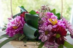Mazzo moderno dei fiori in tonalità viola in un canestro wattled fotografia stock libera da diritti