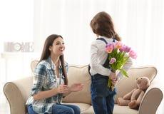 Mazzo nascondentesi del tulipano della bambina per la mamma dietro fotografie stock libere da diritti