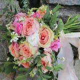 Mazzo nuziale che si trova sulle pietre Il mazzo di nozze delle rose della pesca da David Austin, rosa della unico testa è aument immagini stock libere da diritti