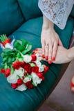 Mazzo nuziale di nozze con bianco e le rose rosse in sue mani su fondo blu Fotografie Stock