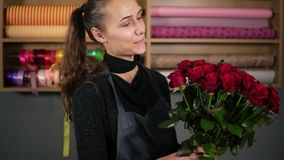 Mazzo perfetto delle rose rosse dal fiorista professionista: giovane fiorista femminile attraente che tiene un mazzo di bello archivi video