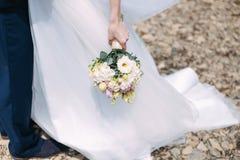 Mazzo piacevole di nozze in mano della sposa Immagine Stock