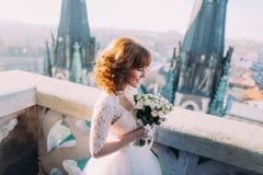 Mazzo rosa della tenuta elegante della sposa sul balcone della torre di vecchia cattedrale gotica Fotografie Stock Libere da Diritti