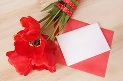 Mazzo rosso dei tulipani con il card&envelope del Libro Bianco su tabl di legno Fotografie Stock