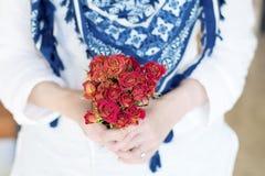 Mazzo rosso delle rose di fioritura nelle mani Fotografie Stock Libere da Diritti