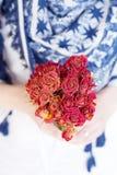 Mazzo rosso delle rose di fioritura nelle mani Immagine Stock Libera da Diritti