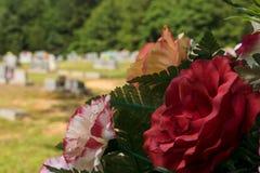 Mazzo rosso sottomesso di disposizione dei fiori al cimitero fotografia stock