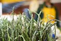 Mazzo selvaggio verde delle teste di punta dell'asparago sulla stalla del mercato fotografia stock
