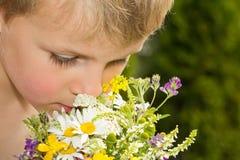 Mazzo sentente l'odore del giovane ragazzo dei Wildflowers Fotografia Stock Libera da Diritti