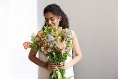 Mazzo sorridente della tenuta del fiorista africano tenero della ragazza dei alstroemerias sopra la parete bianca Occhi chiusi Fotografie Stock Libere da Diritti