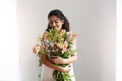Mazzo sorridente della tenuta del fiorista africano tenero della ragazza dei alstroemerias sopra la parete bianca Occhi chiusi Fotografia Stock Libera da Diritti