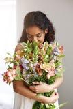 Mazzo sorridente di fiuto della tenuta del fiorista africano della ragazza dei alstroemerias sopra la parete bianca Occhi chiusi Fotografie Stock Libere da Diritti