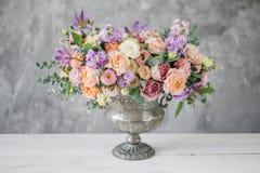 Mazzo splendido dei fiori differenti disposizione floreale in vaso d'annata del metallo Posponga la regolazione colore della pesc fotografie stock libere da diritti