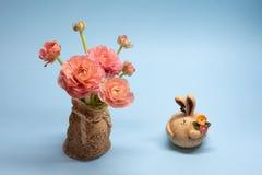 Mazzo sveglio dei ranuncoli e delle figurine rosa delicati della lepre su un fondo blu immagini stock libere da diritti