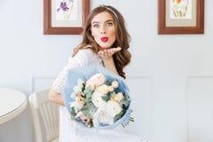 Mazzo sveglio della tenuta della donna dei fiori e di invio del bacio fotografia stock libera da diritti