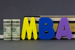 MBA degree is an education investment. Graduate degree MBA letters with dollar currency in front of books on gray background. Advance degree is a education royalty free stock photography