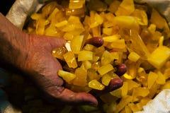 Âmbar na mão Em um fundo escuro Âmbar do close-up Âmbar para o anúncio e as vendas Pedra colorida Fotografia de Stock Royalty Free