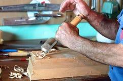 Möbelsnickare som snider ett stycke av trä med stämjärnet Arkivfoton