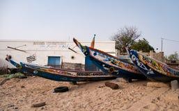 Mbour Senegal: Färgglade fiskebåtar som strandas i sanden arkivbilder