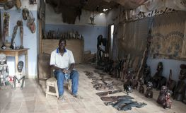 Mbour, Senegal, handcrafts seller posing inside his small souvenir shop royalty free stock photo