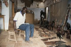 Mbour, Senegal, handcrafts sprzedawcy pozuje wśrodku jego małego sklepu fotografia stock