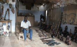 Mbour, Senegal, vendedor de las artesanías que presenta dentro de su pequeña tienda de souvenirs foto de archivo libre de regalías