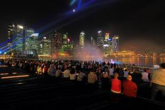 MBS light show Singapore. The public enjoying the light show at MBS with the city nights cape as the back drop. The light show named Wonder full lasted for Royalty Free Stock Image