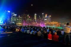 MBS light show Singapore. The public enjoying the light show at MBS with the city nights cape as the back drop. The light show named Wonder full lasted for Royalty Free Stock Photos