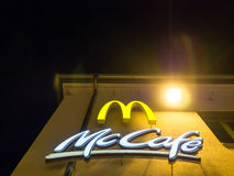 Mc Donald's at night. Mc Donalds and McCafé signs on a building during night time - copy space above Stock Photo
